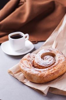 Uma xícara de café expresso em um pires e uma massa folhada uma king size