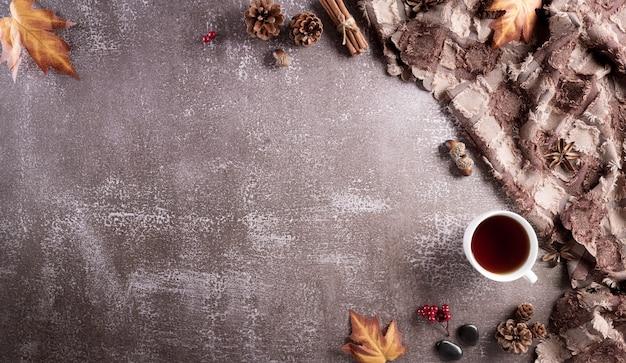 Uma xícara de café flores de algodão, folhas de outono e lenço em fundo de pedra escura