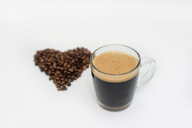 Uma xícara de café fresco e um coração feito de grãos de café