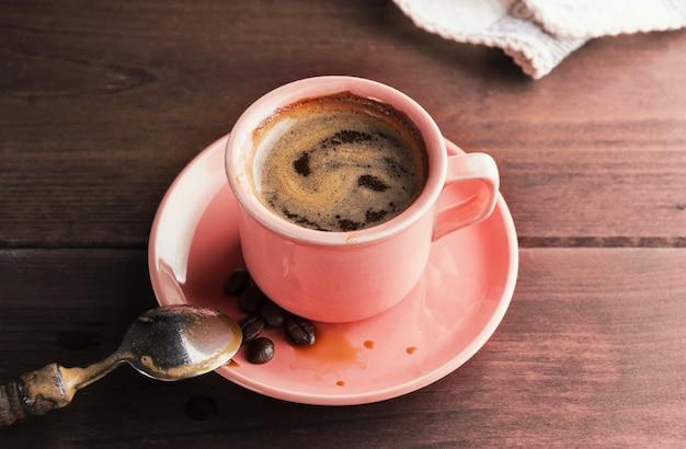 Uma xícara de café fresco, mexida com uma colher, fica sobre uma mesa de madeira. conceito de café, café da manhã ou pausa em um dia ensolarado