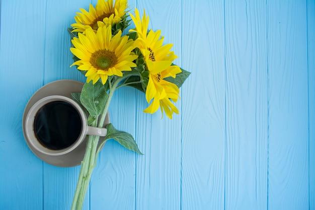 Uma xícara de café, grãos de café, canela e girassol em um fundo azul. clima de verão.