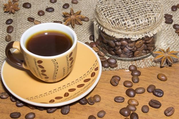 Uma xícara de café, grãos de café no saco