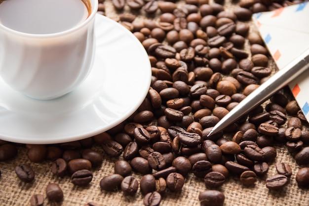 Uma xícara de café, grãos de café; uma carta e uma caneta na mesa