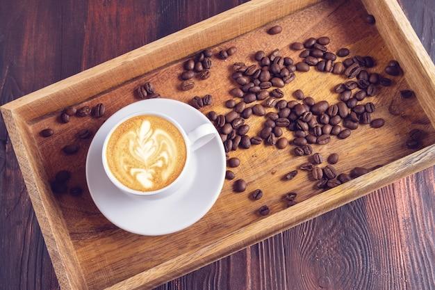 Uma xícara de café latte art e grãos de café próximos em uma caixa de madeira sobre uma mesa de madeira escura.