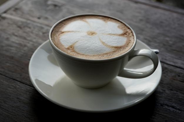 Uma xícara de café latte art quente em uma mesa de madeira