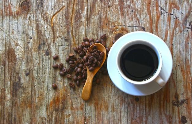 Uma xícara de café na mesa de madeira com grãos de café e colher de pau
