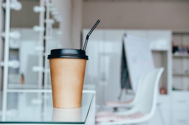 Uma xícara de café na penteadeira perto de espelho na sala de maquiagem