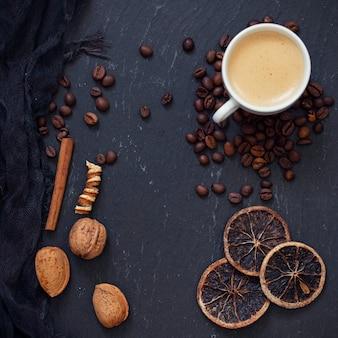 Uma xícara de café na superfície preta com nozes, grãos de café e especiarias