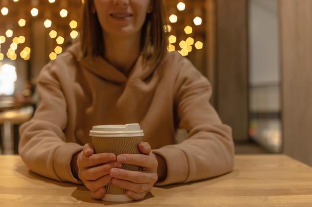 Uma xícara de café nas mãos de uma garota sentada à mesa em uma praça de alimentação