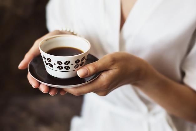 Uma xícara de café nas mãos