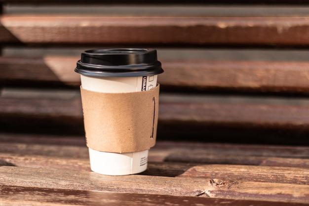 Uma xícara de café no banco de madeira no parque da rua