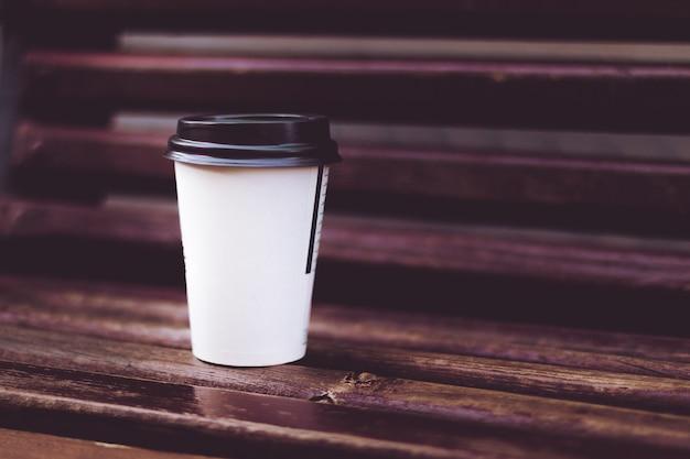 Uma xícara de café no banco de madeira no parque