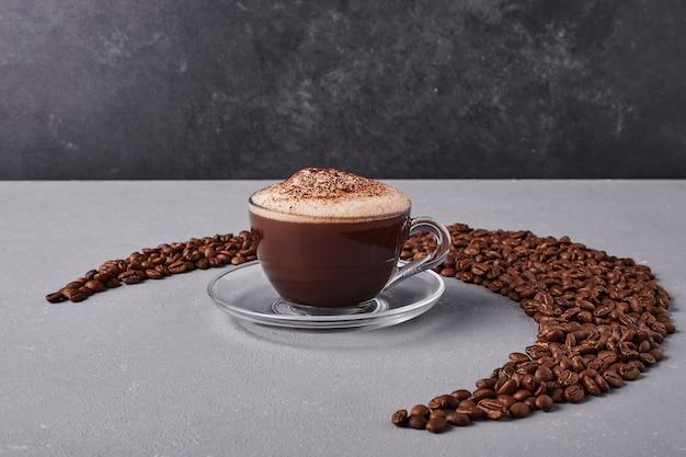 Uma xícara de café no meio de grãos de arábica.