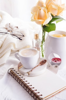 Uma xícara de café no notebook, rosas, vidro e vela
