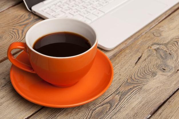 Uma xícara de café no prato laranja em cima da mesa de madeira. interior do escritório