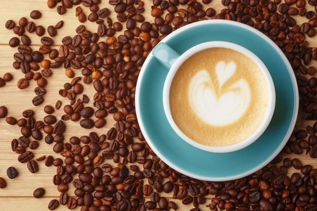 Uma xícara de café perfumado em espuma sobre uma mesa de madeira. latte art. grãos de café.