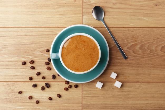 Uma xícara de café perfumado em espuma sobre uma mesa de madeira.
