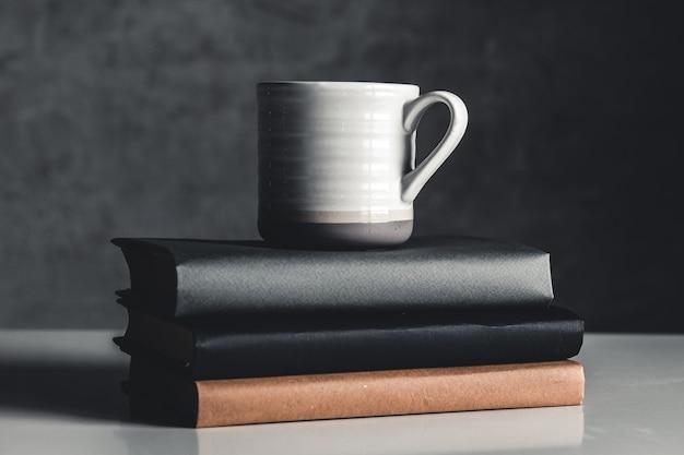 Uma xícara de café perto de uma pilha de livros sobre fundo cinza