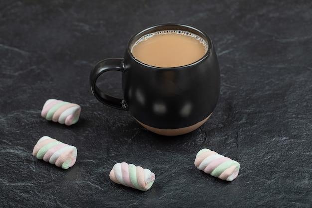 Uma xícara de café preta com marshmallows em uma superfície escura.