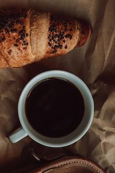 Uma xícara de café preto com um croissant de chocolate estética nos detalhes tons aconchegantes bege e marrom