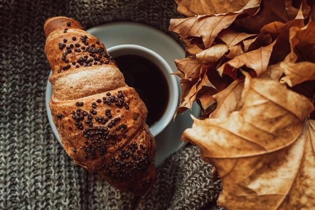 Uma xícara de café preto com um croissant em uma aconchegante natureza morta outonal estética nos detalhes