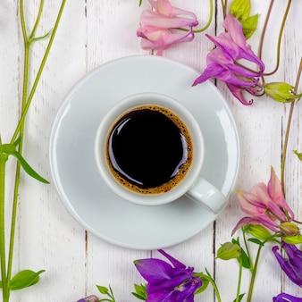 Uma xícara de café preto em um pires e flores em uma mesa branca