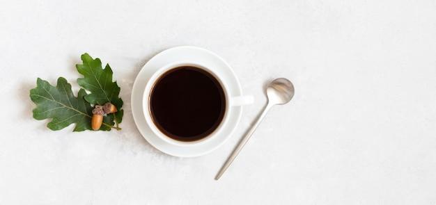 Uma xícara de café preto, folhas de carvalho e bolotas em um fundo branco. café de bolota sem cafeína. espaço para texto. vista superior, configuração plana.