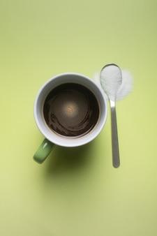 Uma xícara de café preto sem leite e uma colher de adoçante stevia