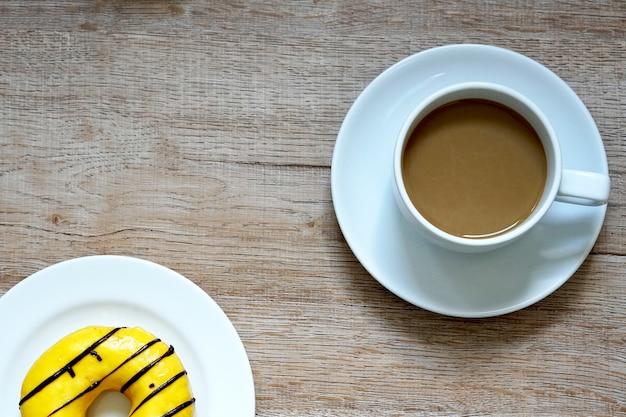 Uma xícara de café quente com donuts doces de cor amarela em fundo de madeira