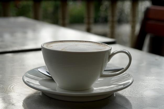Uma xícara de café quente com latte art na mesa