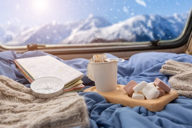 Uma xícara de café quente com marshmallow perto da janela com vista para a montanha de neve