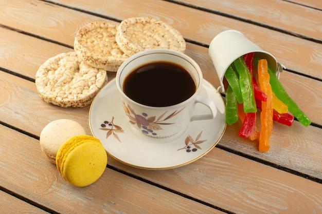Uma xícara de café quente e forte com macarons franceses e geleia na mesa rústica de cor creme beber café forte