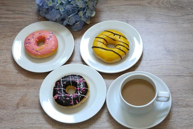 Uma xícara de café quente e uma mistura de donuts doces multicoloridos