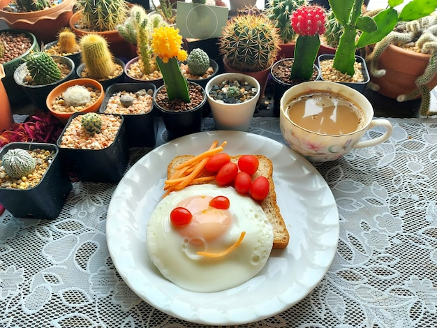Uma xícara de café quente e uma torrada de trigo integral para completar ovos fritos, tomate e cenouras em fatias
