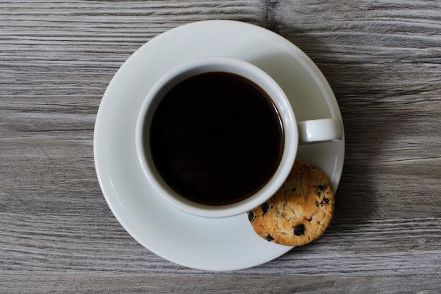Uma xícara de café quente em um pires com um biscoito de chocolate