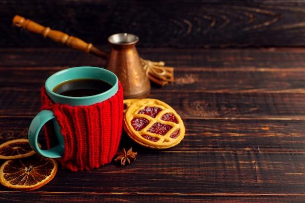 Uma xícara de café quente, em uma capa de malha e biscoitos caseiros