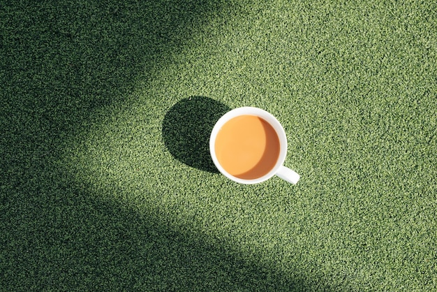 Uma xícara de café quente em uma manhã fria, na grama verde com fundo de orvalho