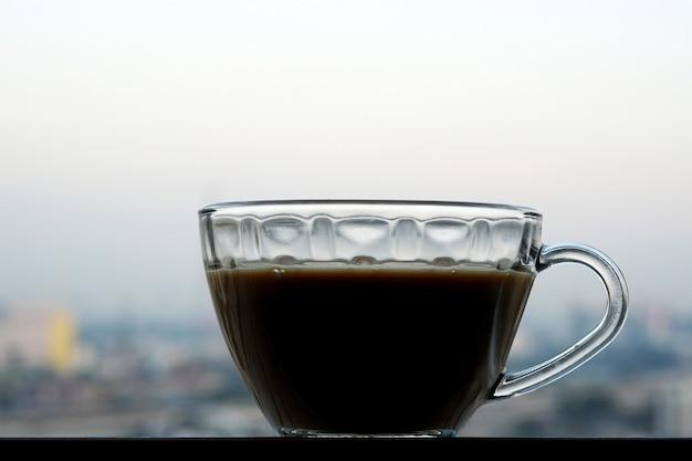 Uma xícara de café quente pela manhã no parapeito da janela de um prédio alto