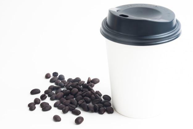 Uma xícara de café quente simulado para marca ou logotipo com grãos de café torrados no fundo branco