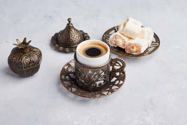 Uma xícara de café servida com lokum turco na mesa branca.