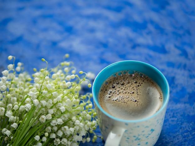 Uma xícara de café sobre um fundo azul e um buquê de lírio do vale. copy space spring café da manhã