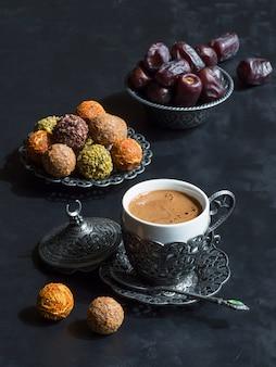 Uma xícara de café turco com doces árabes com datas em uma mesa preta.