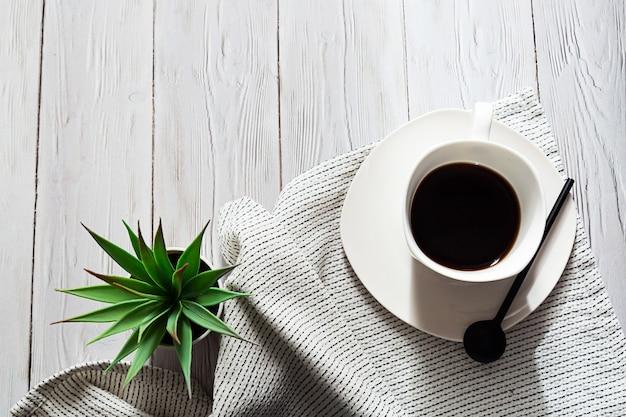 Uma xícara de café, um guardanapo leve e uma planta suculenta em um bule branco sobre uma mesa leve