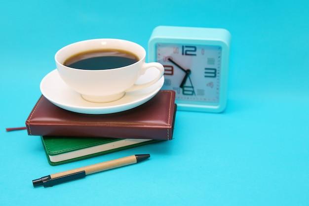 Uma xícara de café, um relógio e um caderno sobre um fundo azul. o conceito do tema de negócios.