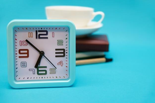 Uma xícara de café, um relógio e um caderno sobre um fundo azul. o conceito do tema empresarial. fazendo as malas no início da manhã. planejamento de trabalho e recreação.