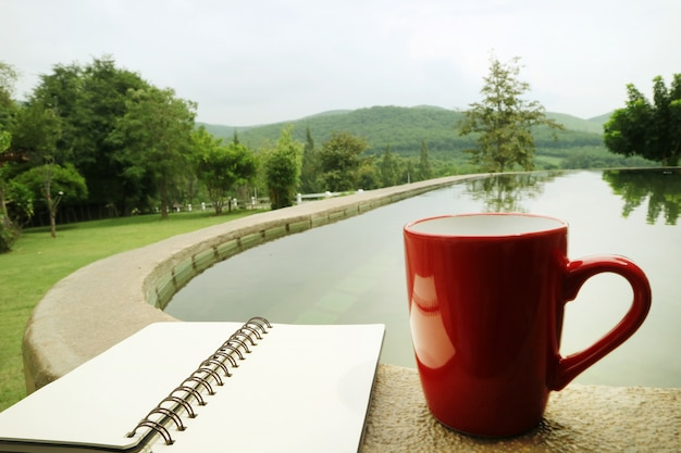 Uma xícara de café vermelha e um notebook estão à beira da piscina em um quintal, com vista para a montanha.