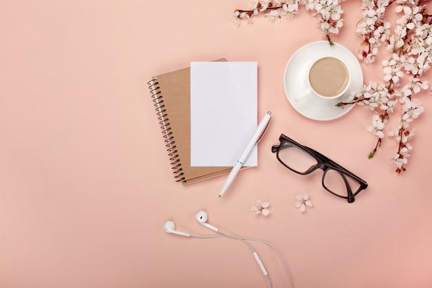 Uma xícara de cappuccino branco com flores de sakura, caderno, fones de ouvido, caneta e óculos