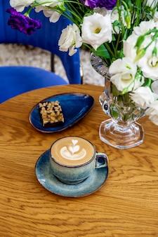 Uma xícara de cappuccino, café e flores em uma mesa em uma foto vertical de café