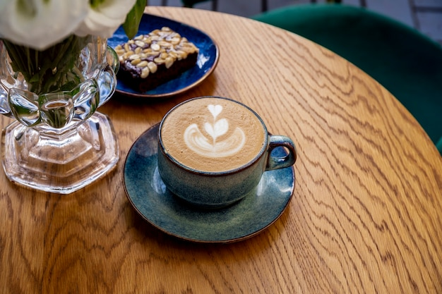 Uma xícara de cappuccino, café e flores sobre a mesa de um café