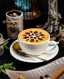 Uma xícara de cappuccino com decoração floral de cacau.